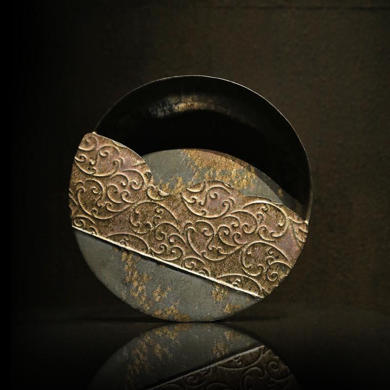 康嘉良 「 墨金 」系列的 作品 以老鐵器斑駁、鏽蝕、焊接修補等樣貌,在簡潔的身形披上墨金的釉衣,如筆畫下的水墨上,灑下鎏金般的金黃,斑駁絢爛的氣質, 陶藝 展現出老鐵器沉著內斂老靈魂的器韻。利用鏽蝕的器物氛圍表達我們對於老器物的愛惜與愛戀,以及器物歷經使用的歷史變化。